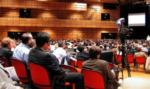 packed conference room with video camera recording